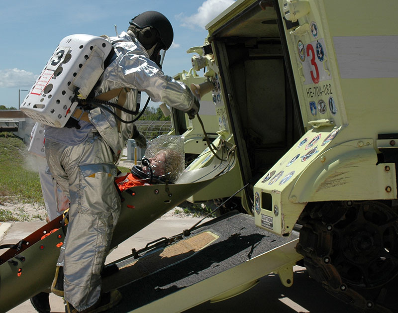 Liquid air pack being used by launch pad rescue team to load simulated patient into M-113, armored personnel carrier. Liquid Air Self-Contained Breathing Apparatus: 1 hour